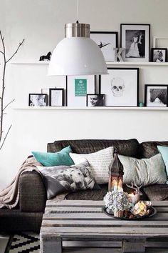 Duas prateleiras estreitas apoiando posters e quadros de tamanhos variados com o tema preto e branco, além de pequenos objetos decorativos