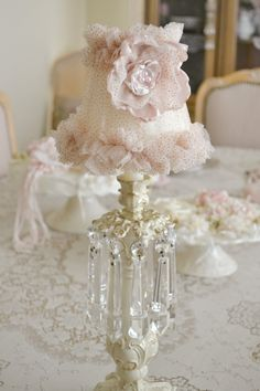 This listing is for one gorgeous small lampshade embellished by Jennelise Rose. Covered in beautiful blush coloured tulle with gold sparkles and embellished with a gillyflower in lovely blush and ivory silk with pale pink pearls in the centre. Measures approx. 5 1/2 tall and 6 wide at the base. Beautiful for a candlestick lamp or on a little wall sconce!   IF YOU WISH TO PURCHASE MULTIPLE VINTAGE ITEMS PLEASE CONTACT ME IN ADVANCE SO THAT I CAN ADJUST SHIPPING CHARGES. IF YOU DO NOT CONTACT…