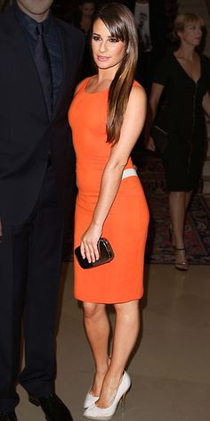 LEA MICHELE  Joining Jessica front row at the Atelier Versace show in Paris, the Glee star vamps it up in an orange cocktail dress with leather inserts, gray pumps and a black clutch, all by Versace. She finishes the look with megawatt Norman Silverman earrings.