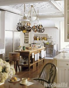 This kitchen is perfect!  I love the ceiling and the hanging copper pots and pans!  I also like how it mixes different materials - wood, marble, steel - so effortlessly.