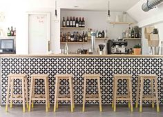 The Hat — Madrid.  The geometric bar front with wooden stools gives a light modern feel to this bar.