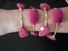 This large fuchsia stone on a gold bangle brings a vibrant pop to your wrist. This girly arm candy is a keeper!