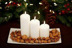Centro de mesa navideño con velas y frutos secos