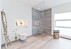 Bright and scandinavian bathroom with large floor tiles and simple interior design.