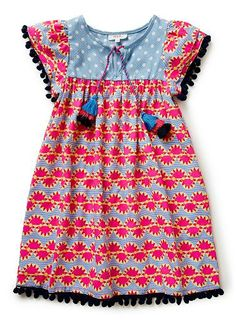 100% Cotton Dress. Features all-over sunray viscose yardage and double layered ruffle sleeve with pom-pom trim on sleeve and hem.
