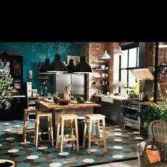Cozinha espaçosa. Tijolos aparentes. Azul petróleo com preto. Ilha para preparo e refeições. Mosaico de cores no piso. Banquetas de madeira. Pendentes industriais.