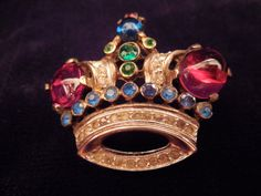 Trifari Crown brooch, famous crown brooch design by Alfred Phillipe. Red glass tones with colored rhinestones, beautiful vintage jewelry