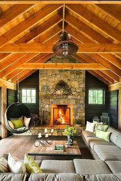 I love everything about this room!! The rustic features of the fire, wooden ceiling and candles; the large sofa and hanging chair; the contrast of the dull grey and bright green...perfect!!!