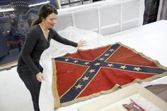 Cathy Wright, curator at the Museum of the Confederacy opens an original battle flag belonging to the 3rd Virginia Infantry in the flag room, which houses hundreds of original civil war battle flags in Richmond, Virginia.