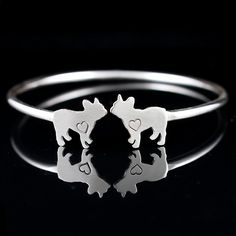 This handmade bracelet is a chic keepsake of your fur-kid. Bracelet was designed and forged out of sterling silver for a comfortable fit. After each french bulldog silhouette was hand sawed they were stamped with a heart symbol and then were fused (attached through heat) to the end of sterling cuff. Careful oxidized detail was added to the heart stamp so the symbol is evident. Cuff was then polished. Adjust once to fit, but frequent adjustment is not recommended, as it will weaken the…