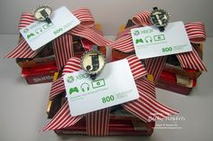 Gifts tied with wide ribbon and painted clothespin with bottle cap letter used to clip gift tag or extra goodie to present.