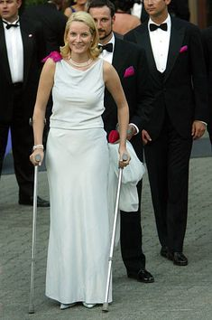 Norwegian Princess Mette Marit leaves a reception hosted by the Norwegian government on crutches May 2002 in Trondheim, Norway. The couple is attending the wedding of Norwegian Princess Martha. Crutches, Reception, Trondheim Norway, Princess, Formal Dresses, Couples, Wedding, Leaves, Crown