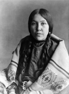Head and shoulders studio portrait of a Native American (Crow) woman, identified as Carries the Warstaff. She wears a loose dress and belt under a heavy woven blanket, a necklace with a star in a crescent moon pendant, long braids, and earrings. Native American Beauty, Native American Photos, Native American Tribes, Native American History, American Indians, American Crow, Cherokees, Into The West, Navajo