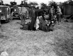 Dans un poste de secours (à droite des toiles de tente), des blessés étendus dans leurs civières à l'air libre attendent leur transfert, roulés dans leurs couvertures. Une nurse ou une volontaire de l'American Red Cross tend un petit réconfort à l'un deux. A gauche des ambulances Dodge WC54 de l'US Medical Corps. Plusieurs GI's dont un officier (marque blanche verticale à l'arrière du casque).