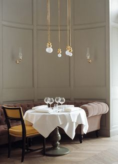 Delicate brass and exposed bulbs, like jewelry. Grand Hotel Stockholm, dining room - Ilse Crawford