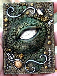 """Polymer clay with a watch face for the eye and 2 Zealandia fossilized ivory or bone and silver jewelry pieces. Colors are metallic paint. Size is 2.5"""" x 3.5"""" or the size of a baseball playing card...."""