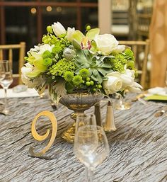Green wedding centerpiece with succulents and cymbidium orchids by Laurel Designs