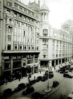 Gran Via A la derecha, los almacenes Madrid-París, imitación de las galerías Lafayette de la capital francesa. A la izquierda, en una calle atravesada por coches sacados del Chicago de los gánsteres, el señorío del hotel Alfonso XIII.