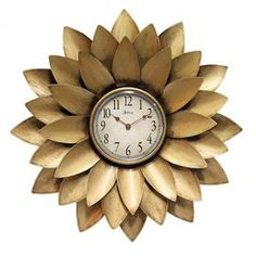 "Metal wall clock with flower-inspired frame in gold.   Product: Wall clockConstruction Material: Iron and glassColor: Antique goldAccommodates: Batteries - not includedDimensions: 20"" Diameter x 3"" D"