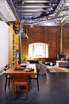 Living comedor integrado en un loft industrial en amarillo, gris y ladrillo. El hogar de un diseñador de moda francés en Villa Crespo.