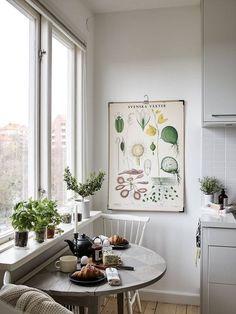 Petit coin repas dans une petite cuisine, face à une grande fenêtre avec sue sur la ville