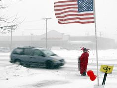 A Liberty Income Tax character stands in the blowing snow along Summit Street in Elgin. He had been standing on the street for about 2 hours and planned to head home soon.