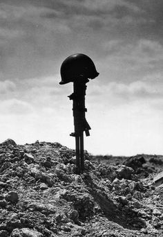 A hero rests. A makeshift memorial to a fallen soldier. Normandy, 1944.