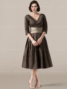 Tea length mother of the bride dress features in taffeta with 3/4 length sleeves, ruched cummerbund waistband coordinated with a V-neck and V-back, Tea-length skirt. Dress & Sash each available in 60 colors, shown in Mocha / Cafe.