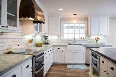 Other new features in the kitchen include white cabinets extending to the ceiling, concrete countertops, subway tile and an antique copper vent hood.