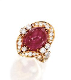 AN 18 KARAT GOLD, RUBY AND DIAMOND RING, VAN CLEEF & ARPELS. Centered by an oval-shaped cabochon ruby weighing approximately 16.00 carats, framed by numerous round diamonds weighing approximately 1.60 carats, size 4½, signed Van Cleef & Arpels.