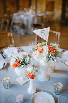 Orange and white flowers in white vases