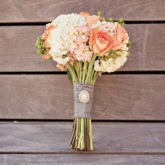 Orange and peach roses with white hydrangeas. -