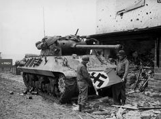 M10 Wolverine tank destroyer crew of Patton's Third Army roll up a Nazi flag they have taken as a trophy after the capture of Bitburg, February 1945.