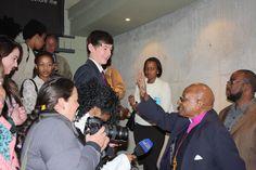 Archbishop Emeritus Desmond Tutu high-fives the crowd at the Maropeng exhibiton during his visit on July 31