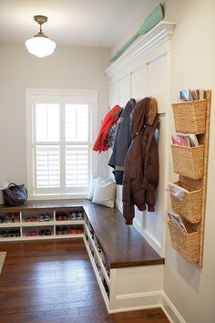 source: Britt Lakin Photography  Benjamin Moore Wickham Gray. Mudroom design with schoolhouse pendant over built-in bench with built-in shoe cubbies next to wall-mounted pocket organizers.