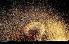 Ein Schmied schleudert in der chinesischen Stadt Nanquan eine Schöpfkelle voll geschmolzenen Metalls auf kalten Stein. Dabei entsteht der prächtige Funkenregen. In dem Ort ist diese Form des Funkenflugs seit mehr als 300 Jahren Tradition.