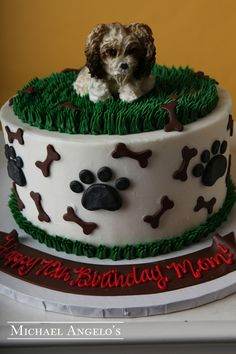 Dog Bones  Prints #7Animals  This cake is iced in buttercream and decorated with fondant bones and paw prints made from buttercream. The dog is also made by hand from buttercream and airbrushed to look true to life.