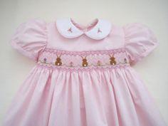 Unadorabile piccola Pasqua vestito per qualsiasi bambina! Fatto di un tessuto molto morbido di colore rosa perla con bianco peter pan collari bordati in tubazioni rosa. Nido dape bella foto tutta la parte anteriore dispone di incantevoli sfumature di rosa, lavanda, verde chiaro e