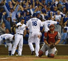 Kansas City Royals players Norichika Aoki (left) Billy Butler and Lorenzo Cain across home plate after Alex Gordon hit a double to score three runs in the first inning against Los Angeles Angels at Sunday's ALDS playoff baseball game on October 5, 2014 at Kauffman Stadium in Kansas City, MO.