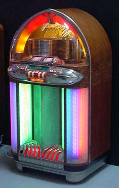 """Another classic juke from Wurlitzer, this one is the 1100 model, produced in 1947. Nicknamed """"The Bomber"""" because of its unique shape, this beauty was loaded with eye-candy! Lots of great deco chrome, rotating colored cylinders and ornately painted murals kept you mezmorized as you listed to one of 24 of your favorite tunes! 3 plays for 25 cents, by the way."""