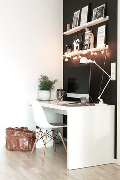 Black wall // light wooden shelves // hanging lights // white chair // white minimal desk // white potted plant