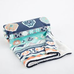The Phoenix Blanket has an Aztec inspired pattern in navy, aqua and orange printed on a soft velour front with a faux fur back and mini pom-pom trimmed edge. Perfect for stroller rides, bundling or simply a boho accent to the nursery.