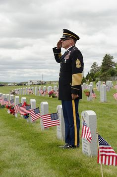Command Sgt Maj Harley Schwind salutes as the flags are raised to full staff during the 2012 Memorial Day Ceremony at the North Dakota Veterans Cemetery on May 28. About 1500 people attended the annual event.