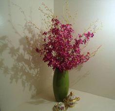 Arranjo em vaso de vidro verde, com dez galhos de orquídeas,musgos. R$ 208,00