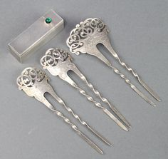 An Art Deco silver engine turned lipstick with hinged mirror and cabochon cut knot, together with