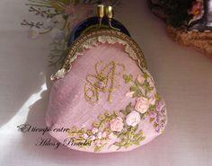 Cartera de boquilla.        En lino rosa, bordada con cintas de seda y...         con inicial bordada en hilo dorado.           Los mat...