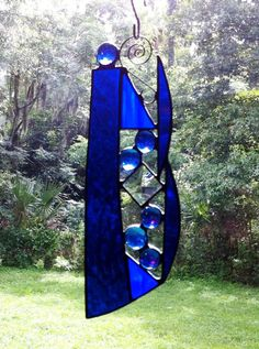 You are looking at a Custom designed Abstract Stained Glass Sun Catcher that is one of a kind! No one else will have one like it and it truly a beautiful piece. This Suncatcher is approximately 8 1/2 high (including scroll hanger) x 3 wide at the widest point. It is made of a combination of a textured Cobalt Blue, blue cathedral glass and iridescent blue glass. The glass is accented with a scroll metal hanger at the top. It has six glass nuggets complimented by a glass bevel. The iri...