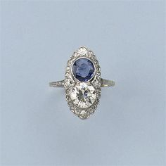A BELLE EPOQUE SAPPHIRE AND DIAMOND RING The navette-shaped front set with a circular-cut sapphire and diamond surrounded by smaller stones, circa 1920