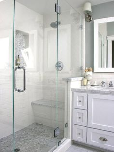 White and Gray walk in shower with white cabinet, seat, nickel fixtures,