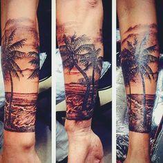 tatuaje hermosa playa brazo.  Las palmeras están bien dibujados, así como las olas de la playa detrás de él, toda la escena representa a una playa muy tranquila.